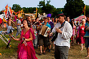 Celebration to close the Glastonbury festival with a man and woman leading a musical procession within the peaceful atmosphere of the Healing Area of the Green fields. There is an exciting blend of healing arts and spiritual/therapeutic orientations as well as fiery celebrations and play. The area is designed as an elemental mandala of Fire, Air, Earth and Water. Each of these circles express a distinct quality of healing which you can experience as you move through the field.
