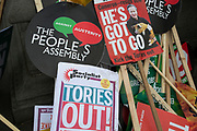 Pile of placards at the Peoples Assembly Against Austerity demonstration against cuts for health, homes, jobs and education on Saturday April 16th in London, United Kingdom. Tens of thousands of people gathered to protest in a march through the capital protesting against the Conservative Party cuts. Almost 150 Councillors from across the country have signed a letter criticising the Government for funding cuts and and will be joining those marching in London. The letter followed the recent budget in which the Government laid out plans to cut support for disabled people while offering tax breaks for big business and the wealthy.