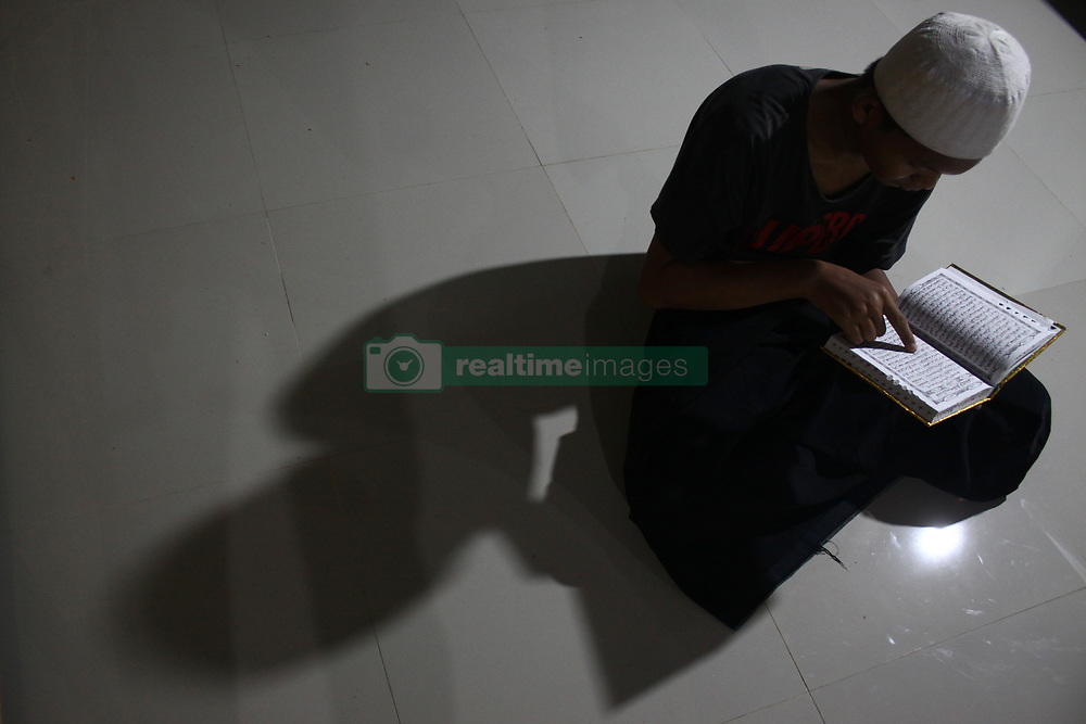 June 2, 2017 - Bekasi District, West Java, Indonesia - A young man reading Quran after following Taraweh prayer at the Jammi Annawawiyyah mosque during the holy month of Ramadhan, Muslims in Indonesia often their times in the mosque to perform various worship besides salat called I'tikaf, one of them by reading Quran. (Credit Image: © Tubagus Aditya Irawan/Pacific Press via ZUMA Wire)