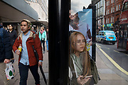 Young woman with defined eyebrows on her smart phone at a bus stop on Oxford Street in London, England, United Kingdom.