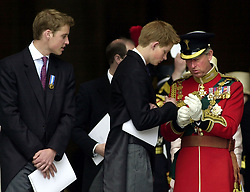 File photo dated 3/5/2002 of Prince William watching his brother, Prince Harry, help his father, the Prince of Wales, adjust his gloves as they leave St Paul's Cathedral after a service of Thanksgiving to celebrate to the Golden Jubilee of Britain's Queen Elizabeth II.