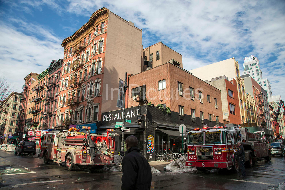 Two classic red Fire Department of New York FDNY engine trucks drive through the intersection between Ludlow Street and Rivington Street in Manhattan, New York City, New York, United States of America.