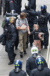"© Licensed to London News Pictures . 11/06/2013 . London , UK . A man , a woman and a young boy carrying a stuffed toy elephant are escorted from the building by riot police . Police surround a former police station on 40 Beak Street , Soho this morning (11th June) which has been occupied by organisers as a base for today's "" Stop G8 "" anti capitalist protest . Demonstrations in London today (Tuesday 11th June 2013) ahead of Britain hosting the 39th G8 summit on 17th/18th June at the Lough Erne Resort , County Fermanagh , Northern Ireland , next week . Photo credit : Joel Goodman/LNP"
