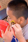 Face painter decorating young Asian American boy. Dragon Festival Lake Phalen Park St Paul Minnesota USA