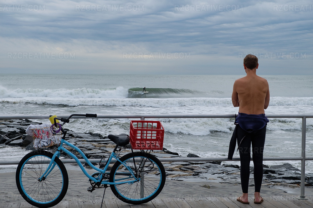 A surfer in Ocean City, New Jersey watches from the boardwalk as another surfer rides a wave on a fall day. Photo © Robert Zaleski / rzcreative.com