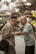 Two old friends greet and share a joke with each other in the Mahane Yahuda Market, Jerusalem, Israel