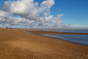 Cumulus clouds over coastline at end of Orford Ness spit, Shingle Street, Suffolk, England, UK
