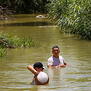 Juan Jose Garcia, left, and Jose Garcia wade away from where the two found a small deceased child floating in a irrigation canal while drag fishing for tilapia north of Edinburg. Hidalgo County Sheriff deputies where searching nearby for the child who was involved in a vehicle accident with his parents Sunday morning. <br /> Nathan Lambrecht/The Monitor