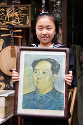 Young girl holding portrait of Chairman Mao outside art gallery in Shanghai China