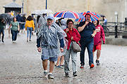 Tourists with umbrellas walking near the Tower of London during rain and wet weather in London, England on August 10, 2018