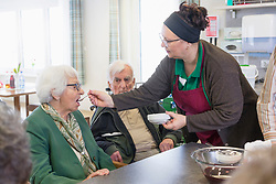 Nurse giving food to taste to senior woman in rest home