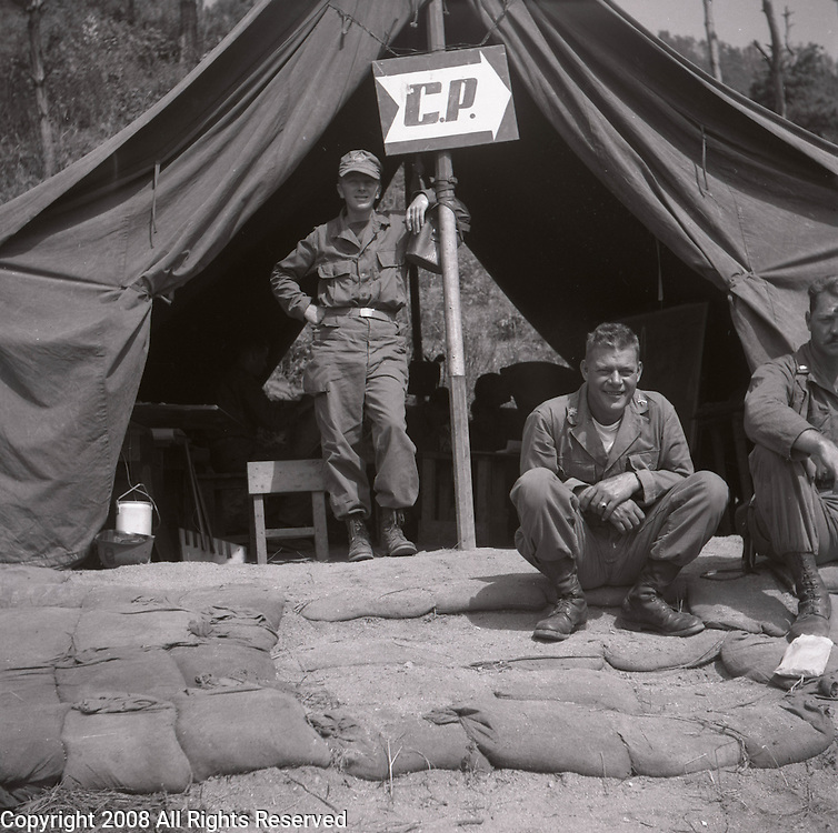 A Major in the U.S. Army, Second Infantry Division, right sits while a Captain stands at the entrance of a command post tent during the Korean War.  These are photos of the 2nd Infantry Division in the Korean War in 1950 or 1951.