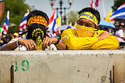 """09 DECEMBER 2013 - BANGKOK, THAILAND:  Thai anti-government protestors against a barricade in front of Government House in Bangkok. Thai Prime Minister Yingluck Shinawatra announced she would dissolve the lower house of the Parliament and call new elections in the face of ongoing anti-government protests in Bangkok. Hundreds of thousands of people flocked to Government House, the office of the Prime Minister, Monday to celebrate the collapse of the government after Yingluck made her announcement. Former Deputy Prime Minister Suthep Thaugsuban, the organizer of the protests, said the protests would continue until the """"Thaksin influence is uprooted from Thailand."""" There were no reports of violence in the protests Monday.     PHOTO BY JACK KURTZ"""