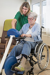 Nurse with senior woman on wheelchair exercising on exercise bike in rest home