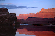 """The Vermilion Cliffs of the Paria Plateau are reflected in the morning still water of the Colorado River at the """"put in"""" for a Grand canyon river Trip."""