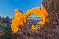 """The Double O Arch is one of the longer hikes in Arches National Park. After reaching the viewpoint on the other side, you have to climb through the """"lower O"""" to reach this view. The light on the arch at sunset was amazing, as was the view of the distant desert.<br /> <br /> Date Taken: 11/6/2013"""