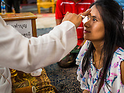 31 AUGUST 2014 - SARIKA, NAKHON NAYOK, THAILAND: A Thai woman is annointed by a Hindu priest at the Ganesh festival at Shri Utthayan Ganesha Temple in Sarika, Nakhon Nayok. Ganesh Chaturthi, also known as Vinayaka Chaturthi, is a Hindu festival dedicated to Lord Ganesh. It is a 10-day festival marking the birthday of Ganesh, who is widely worshiped for his auspicious beginnings. Ganesh is the patron of arts and sciences, the deity of intellect and wisdom -- identified by his elephant head. The holiday is celebrated for 10 days, in 2014, most Hindu temples will submerge their Ganesh shrines and deities on September 7. Wat Utthaya Ganesh in Nakhon Nayok province, is a Buddhist temple that venerates Ganesh, who is popular with Thai Buddhists. The temple draws both Buddhists and Hindus and celebrates the Ganesh holiday a week ahead of most other places.    PHOTO BY JACK KURTZ