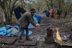 Harefield, UK. 3 February, 2020. Mark Keir of Save Colne Valley chops a block of yew wood at the woodland camp section of Harvil Road wildlife protection camp. Environmental activists from Save Colne Valley and Extinction Rebellion are seeking to prevent construction works for the HS2 high-speed rail link in the Colne Valley which would require the felling of hundreds of mature trees.