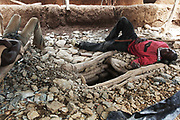 Two men sleeping exhausted next to the entrance to a gold mine shaft. The mines in the small community near Bolgatange in Northern Ghana are dug with shovels and spades and held up by timber, all very precarious. The mine shafts go deep into the ground and run along under the surrounding fields. The small community which has sprung up around the gold finds consists of poor people from all over Northern Ghana,most of them now stuck, not making much money and in dept to their gold dealers.
