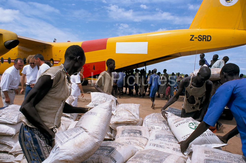 Aid workers unload sacks of Unimix food aid delivered by a De Havilland Buffalo transport plane. Ajiep, Bahr el Ghazal, Sudan. The famine in Sudan in 1998 was a humanitarian disaster caused mainly by human rights abuses, as well as drought and the failure of the international community to react to the famine risk with adequate speed. The worst affected area was Bahr El Ghazal in southwestern Sudan. In this region over 70,000 people died during the famine.