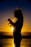 A young woman smoking marijuana in a bong (with Rocky Mountains behind), Littleton, Colorado USA. Colorado was the first state to legalize the sale of marijuana for recreational use in 2014.
