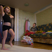 CAPTION: As Yana practises her gymnastics routine, her autistic brother Dmitry quietly watches her during a rare moment in which he is relatively settled. LOCATION: St Petersburg, Russia. INDIVIDUAL(S) PHOTOGRAPHED: Yana Shpunt (left) and Dmitry Shpunt (right).