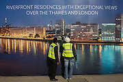 Workmen inspect their construction hoarding, a night time panorama of the Thames south bank, featuring riverside properties on the Thames - the future view of their new skyscraper. The temporary hoarding will stay in place for the time that the company's new residential riverfront apartments are under construction. In the image, the river Thames bends round from Vauxhall on the south bank to Westminster.