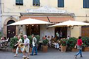 Diners eat al fresco at restaurant and bar Caffe 1888 Fiaschetteria Italiana in Piazza del Popolo, Montalcino, Val D'Orcia,Tuscany, Italy