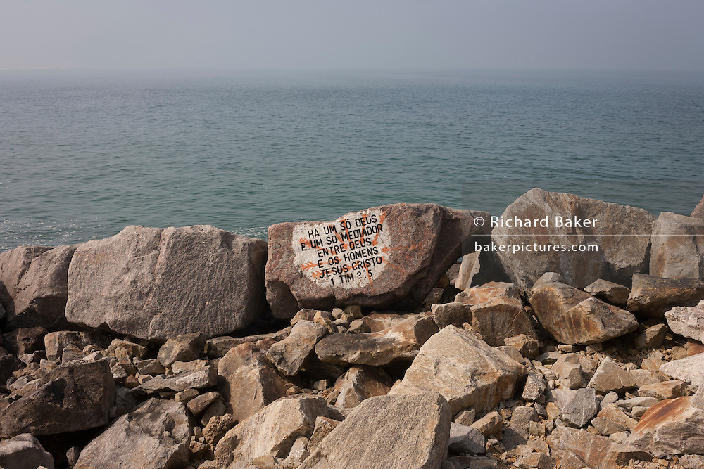"Translated into Portuguese is religious Bible scripture from Timothy 2:5 and painted onto a rock that forms part of the breakwater, on 18th July 2016, on Paredao da Praia da Barra, at Barra, near Aveira, Portugal. In English, it reads: ""For there is one God and one mediator between God and mankind, the man Christ Jesus."" (Photo by Richard Baker / In Pictures via Getty Images)"