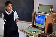 A volunteer from a local private school helping with an IT lesson as part of the Shaishav Trust's Mobile Resource Centre in the Bhavnagara region of Gujarati, India. The Shaishav Trust is trying to provide education and support for children in child labour.