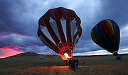 Storm clouds glow from the setting sun as balloonists make a last second attempt to go aloft following a storm at Antelope Island State Park in Utah. Colin Braley/Wild West Stock