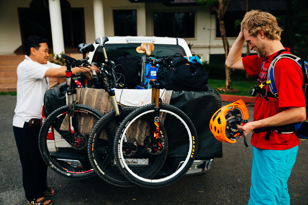Mr. Sak loads the bikes and Andrew Whiteford cools off after a ride in the single track through the jungle near Chiang Mai, Thailand.