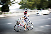 "A Chinese woman rides her bycicle wearing a sunscreen protection helmet in the traffic jam of Beijing, China, July 20, 2014.<br />   <br /> This picture is part of the series ""Urban Chinese Streets"", a journey on the streets of Chinese cities to discover their modern citizens and habits.        <br /> <br /> © Giorgio Perottino"