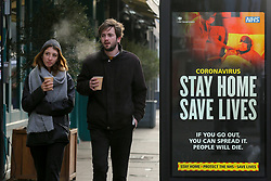 "© Licensed to London News Pictures. 09/01/2021. London, UK. A couple with hot drinking cup walk past the Government's ''Stay Home, Save Lives' Covid-19 publicity campaign poster in north London on a cold morning, as the number of cases of the mutated variant of the SARS-Cov-2 virus continues to spread around the country. The message in the advertising campaign asks people to act like they have Covid and Prime Minister Boris Johnson has said that the public should ""stay at home"". Photo credit: Dinendra Haria/LNP"