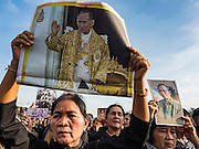 22 NOVEMBER 2016 - BANGKOK, THAILAND:  People hold up photos of the late King of Thailand, including Thai currency which bears a likeness of the King, during a ceremony to honor His Majesty at Sanam Luang Tuesday. Hundreds of thousands of Thais gathered across Thailand Tuesday to swear allegiance to the Chakri Dynasty, in a ceremony called Ruam Phalang Haeng Kwam Phakdi (the United Force of Allegiance). At Sanam Luang, the Royal Parade Ground, and location of most of the mourning ceremonies for the late King, people paused to honor His Majesty by singing the Thai national anthem and the royal anthem.      PHOTO BY JACK KURTZ