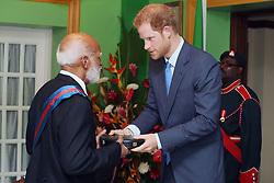 Prince Harry presents to Sir Edmund Lawrence with his GCMG during a reception hosted by Governor-General of Saint Kitts and Nevis Sir Tapley Seaton at Government House, Basseterre, during the second leg of his Caribbean tour.