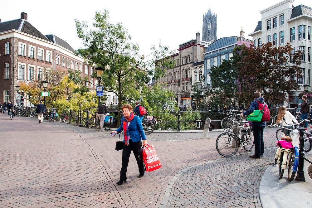 In Utrecht loopt een vrouw met een boodschappentas langs de Oudegracht in het centrum van de stad.<br /> <br /> In Utrecht a woman walks with a shopping bag next to the Oudegracht at the city center.