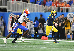 Michigan Wolverines quarterback Shea Patterson (2) scrambles away from the Florida Gators defender during the Chick-fil-A Bowl Game at  the Mercedes-Benz Stadium, Saturday, December 29, 2018, in Atlanta. ( AJ Reynolds via Abell Images for Chick-fil-A Kickoff)