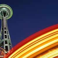 USA, Washington, Seattle, Spinning lights of amusement park rides swirl beneath Space Needle on summer evening