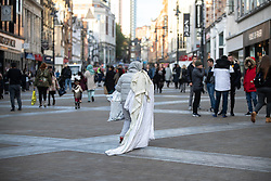 © Licensed to London News Pictures . 24/10/2018. Leeds , UK . A woman walks with a blanket on Briggate , in Leeds City Centre . At least six people sleeping rough have died in the Metropolitan Borough of the City of Leeds since March 2017 and West Yorkshire Police say they responded to 66 reported cases of people suffering the effects of Spice in July 2018 , a large increase on previous months . Photo credit : Joel Goodman/LNP