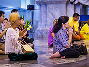 "31 MAY 2017 - CHACHOENGSAO, THAILAND:  People pray in the main ""viharn"" (prayer hall) at Wat Sothon (also spelled Sothorn) in Chachoengsao, Thailand. The temple is one of the largest and most visited in Thailand. People make merit by paying to wrap the Buddha statues in yellow robes. The temple is most famous because people leave hard boiled eggs as an offering at the temple. They ask for business success or children and leave hundreds of hard boiled eggs.     PHOTO BY JACK KURTZ"