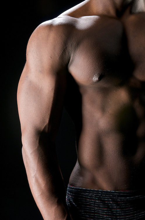 Close up of worked out biceps and abdominals.