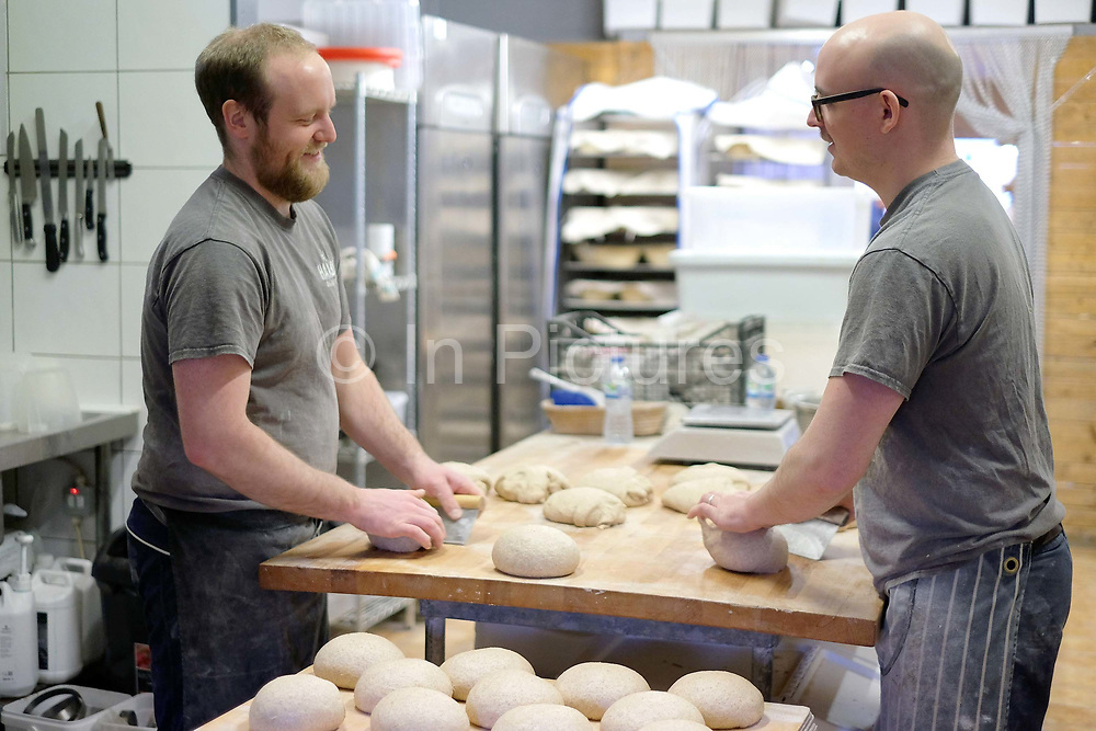 Bakers shaping sourdough bread at the Haxby Bakehouse, Yorks artisan bakery in Haxby, North Yorkshire, United Kingdom on 10th February 2017. Haxby Bakehouse make bread using traditional methods of slow fermentation. They use low yeasted overnight sponges, natural sourdoughlevain or a combination of the two. This means the bread they produce is full of flavour without the use of any artificial flour improvers, preservatives or emulsifiers.