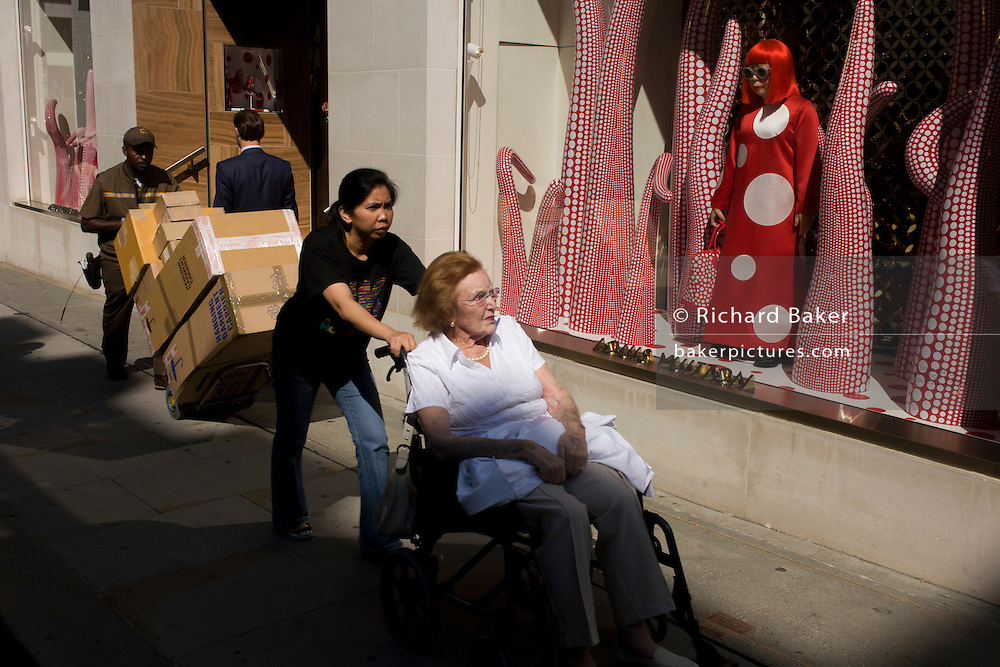 DHL courier and wheelchair-bound lady and her carer passes-by the Louis Vuitton shop window in New Bond Street.  The red theme of the store window acts as a splash of vibrant colour in an otherwise neutral street landscape in central London. The design is a collaboration between Vuitton and the artist Yakoi Kusama, whose tentacle and flower campaign accompanies a life size Yayoi Kusama model.