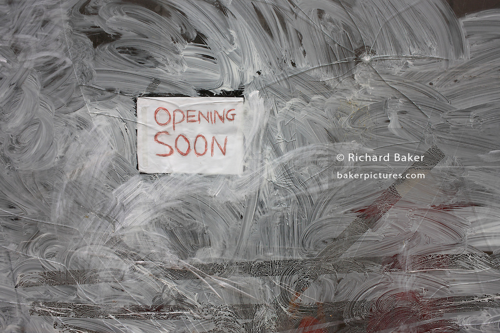 A window in Redchurch Street, East London England, proclaims the opening soon of a business. Using emulsion paint and water to obscure the interior, we see the optimistic sign and the swirls of the window pane. The patterns and shapes inadvertantly traced are confusing and neurotic.