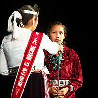 """Kaleigh Shorty, 14, center, a Navajo I student at Crownpoint High School responds to a question posed by Adaliya Archie, 14, Miss Crownpoint High School Diné Princess at the Diné Language & Culture Winter Festival, Wednesday, Dec. 5. at Gallup High School. A recent lesson on the Navajo Code Talkers inspired the question, """"Which relative of yours is a veteran?"""" Shorty responded by using one version of the Navajo Code to spell their name on stage."""
