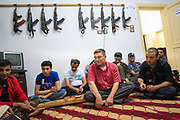 Kalashnikov assault rifles hang on the wall as Free Syrian Army (FSA) member addresses to his fellow men in army at the FSA facilities in Marea on Monday, May 28, 2012. (Photo by Vudi Xhymshiti)