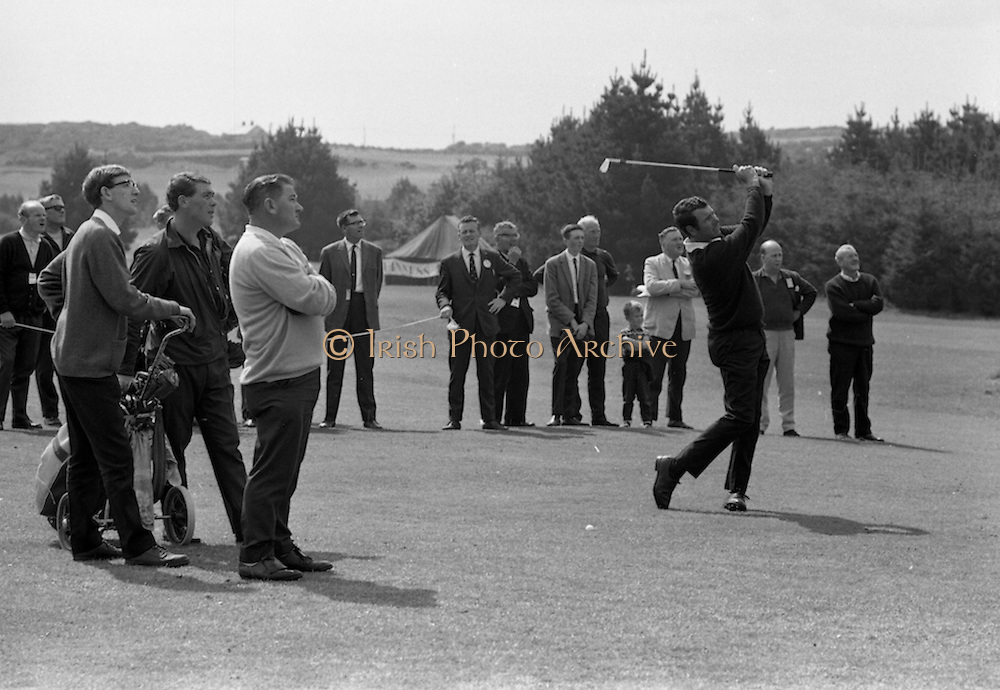 J. Craddock, Foxrock, watches as his partner Hugh Boyle plays his 2nd shot down the fairway at the Irish Dunlop £1,000 Tournament at Tramore Golf Club, Co. Waterford on the 19th August 1967.