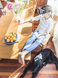 Girl wearing virtual reality glasses in living room with dog relaxing on floor