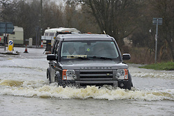 © Licensed to London News Pictures. 11/02/2014. Shepperton and Chertsey, UK. A car on Chertsey Bridge Road.  Flooding in SHEPPERTON AND CHERTSEY in Surrey today 11th February 2014 after the River Thames burst its banks. The Environment Agency has issued 14 Severe Flood Warnings alone the Thames. Photo credit : Stephen Simpson/LNP